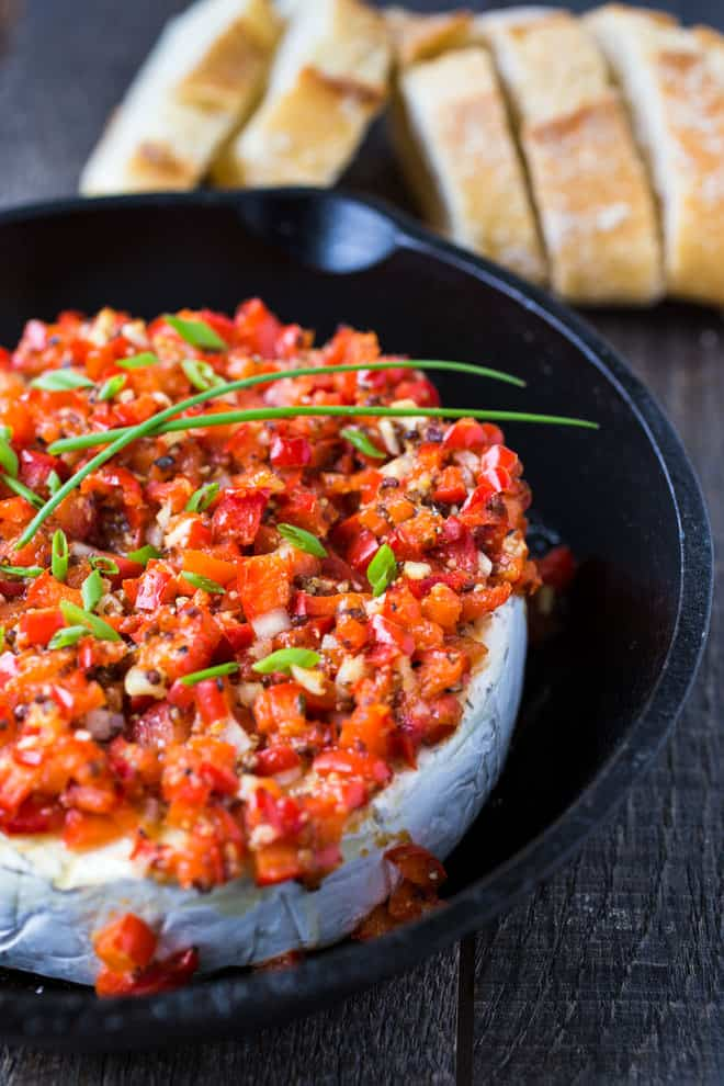 Brie in a cast iron skillet covered with roasted red pepper and garlic.