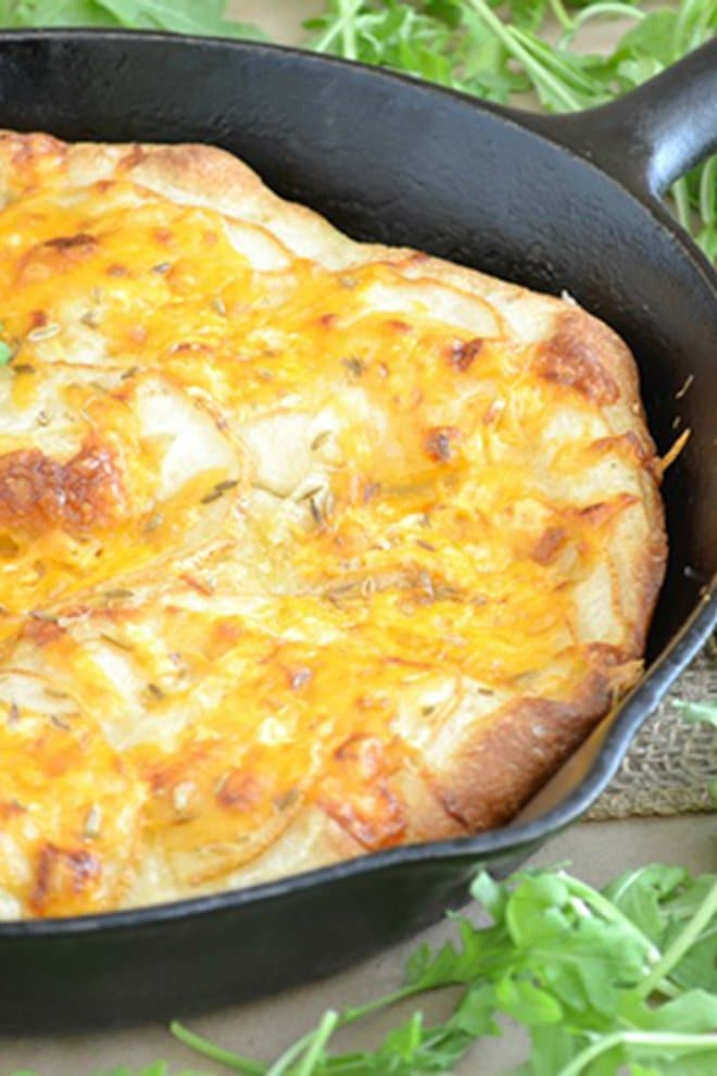 Pizza dough skillet bread is really easy to make. Just place fresh pizza dough into a skillet and I like to top it with cheddar and apples for a twist.