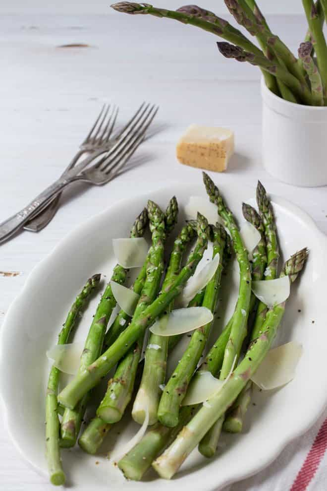 Roasted asparagus and Parmesan cheese shavings on a white platter.