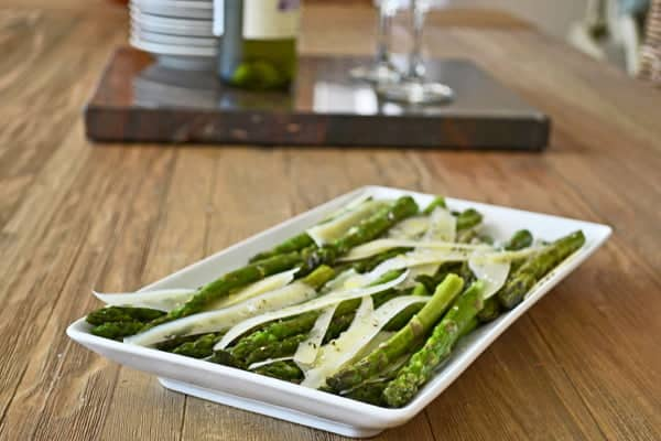 Roasted asparagus with big slivers of Parmesan on a white platter.