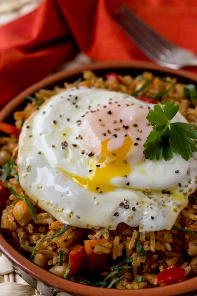 Rice and beans topped with a fried egg with pepper on top.