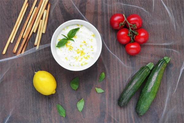 This is a warm goat cheese fondue dip with lemon and basil that uses bread sticks, cherry tomatoes and zucchini as dippers.