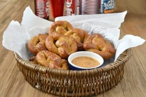 These are homemade soft pretzels made from bough pizza dough. With them is a mustard dipping sauce made of dijon mustard, strawberry jam and sriracha.
