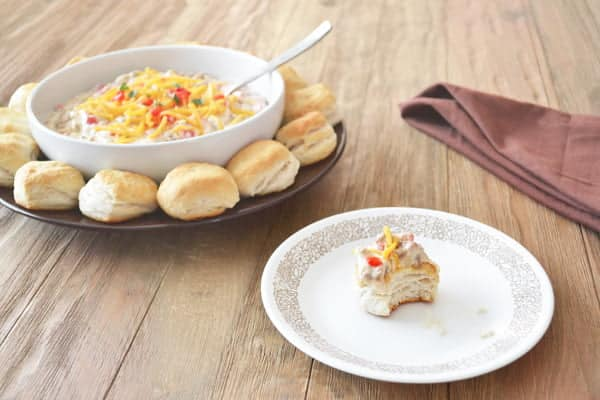 An easy dip recipe for Double Dip Southern Dip, made of crumbled breakfast sausage, roasted peppers, cream cheese and cheddar with a bit of hot sauce. Served with biscuits to dip. Get the recipe on COOKtheSTORY.com