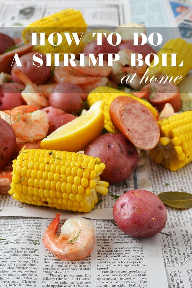 "cooked corn on the cob, shrimp, red potatoes, and sausage in a pile on a newspaper with lemon wedges. The words ""How to do a shrimp boil at home"" are on the image."