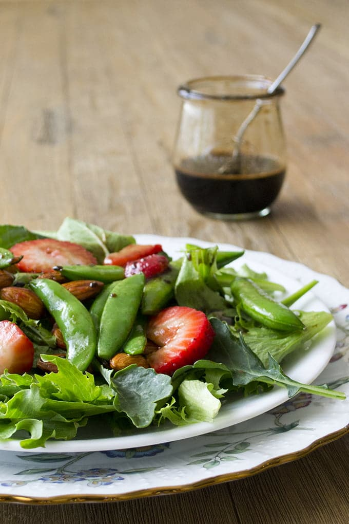 Sautéed Strawberry Salad with Sugarsnap Peas on a white plate with a container of balsamic dressing.
