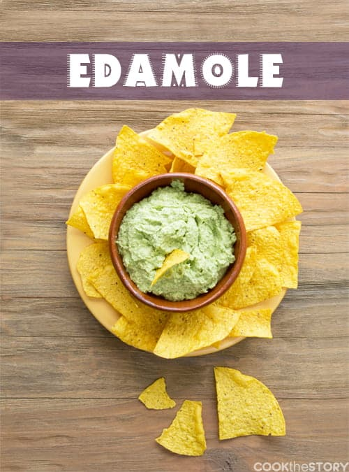 A bowl of green bean dip shot from above. The dip is in a wooden bowl with is on a plate surrounded by tortilla chips. The word Edamole is overlayed over the picture.