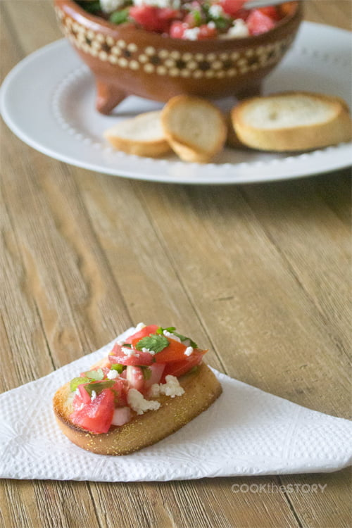 A slice of toasted baguette on a folded white paper napkin. On the baguette is a mixture of tomatoes, onions, cilantro and crumbled queso fresco. In the background there is a white plate with a bowl of the tomato mixture and more slices of toast. The background is a pale wooden table.