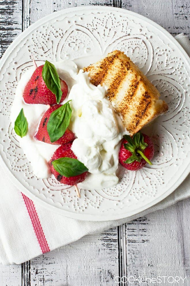 This Grilled Strawberry Shortcake Recipe is a super-easy yet impressive summer dessert. You grill some store-bought angel food cake and you grill some honey-dipped strawberries. Then you top it with a puff of Lemon and Basil Whipped Cream. It tastes like summer!