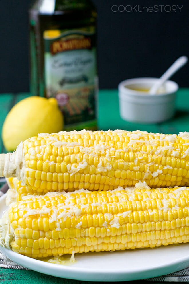 Several ears of corn on the cob topped with olive oil and Parmesan.