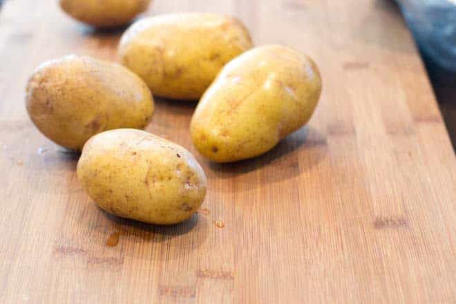 Washed potatoes on a wooden cutting board.
