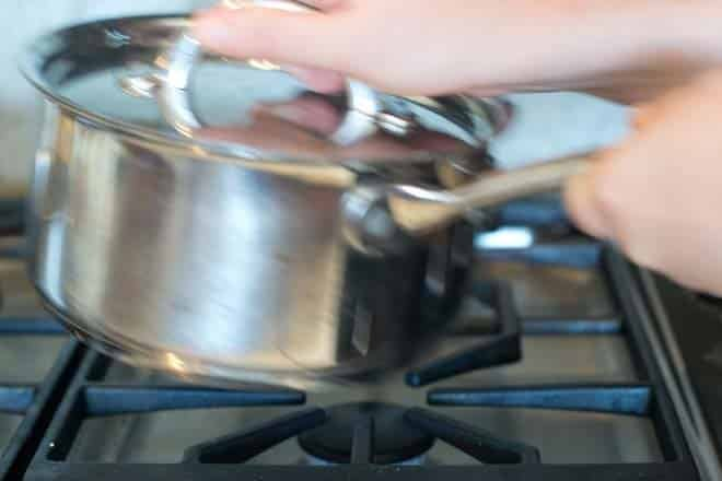 Shaking a pot of potatoes over the stove.