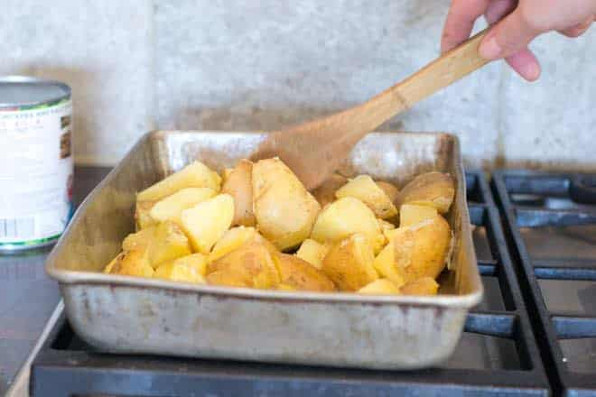 Potatoes in baking pan with oil, being stirred with wooden spoon.