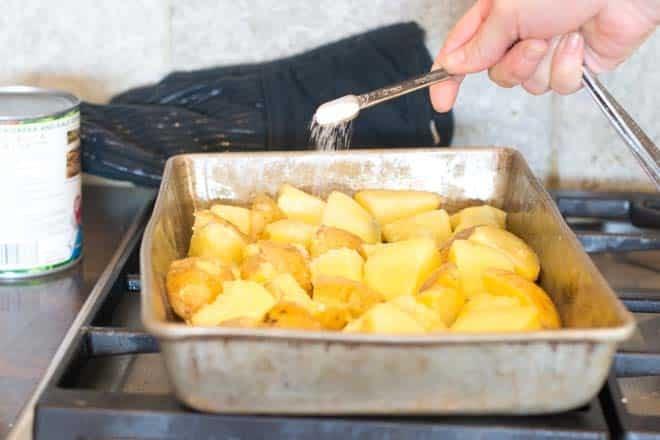 Adding salt to potatoes in baking pan.