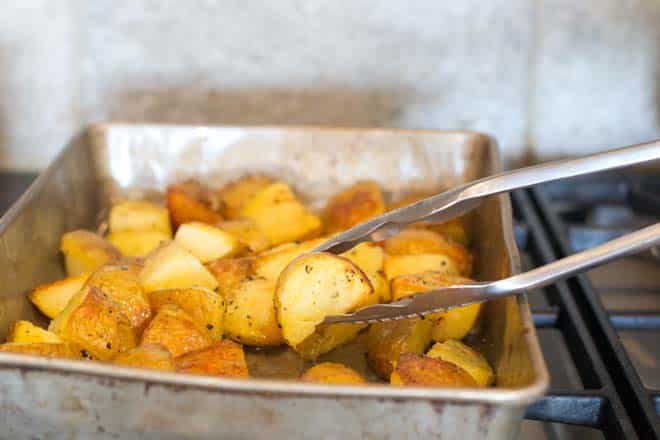 flipping roasted potatoes with tongs to ensure even browning