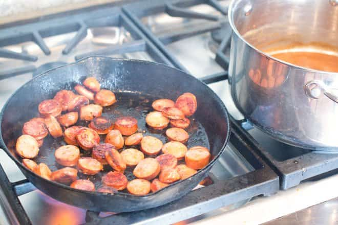 Andouille sausage browning in the pan