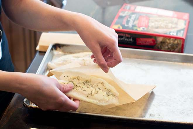 Take the frozen fish fillets out of the box, remove the plastic wrapping, and slide the fillets into the provided parchment paper baking pouches.