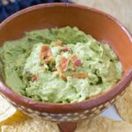A wooden bowl on a white plate. The bowl has a Mexican design on the outside. It contains a green avocado dip that is topped with pieces of crispy bacon. There are tortilla chips around the bowl on the plate.