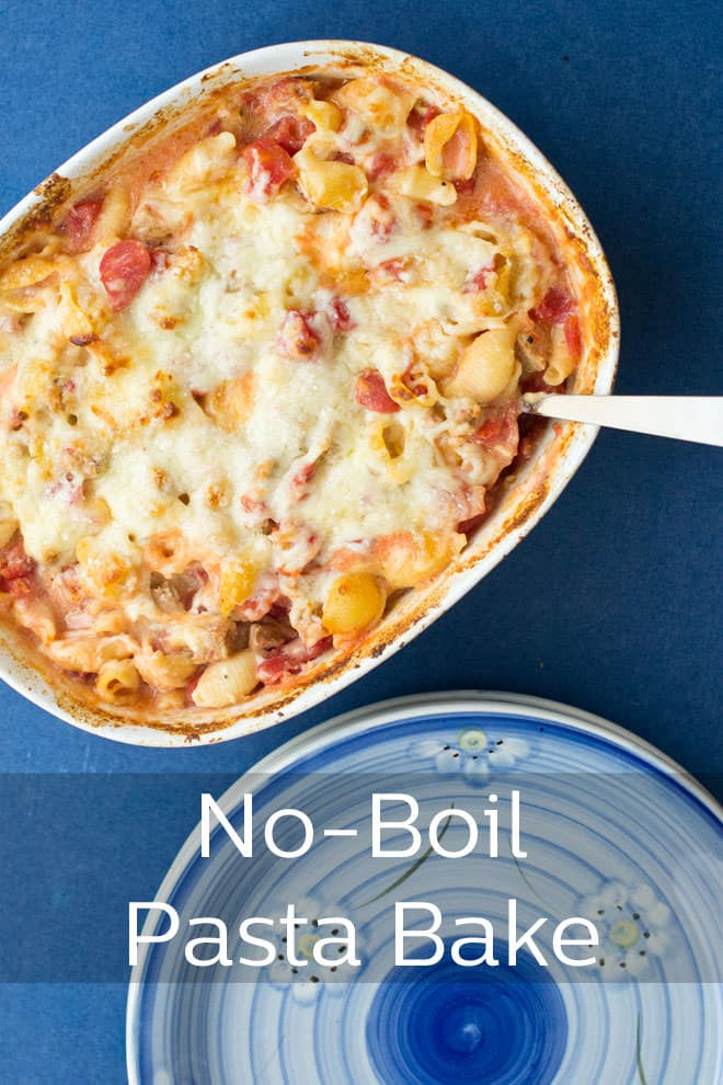 A casserole of baked pasta from above with a serving spoon in the casserole, and a stack of blue plates beside the casserole dish.