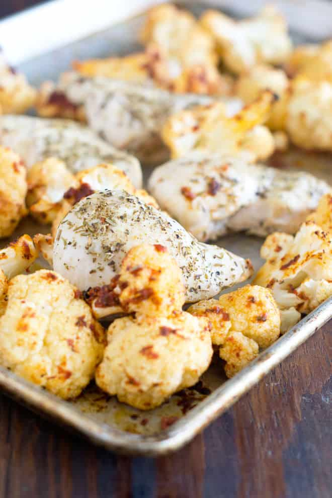 Chicken breasts and cauliflower florets with Italian seasonings on a sheet pan.