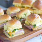 Find out how to make sliders for a crowd with zero fuss. These breakfast sliders are super easy to make because you start with a bunch of attached buns (the kind that are sold all attached to each other) and you build one quick big sandwich. Then you bake it. Once it's hot inside and toasty on top, you cut the buns apart into individual sliders. It's so so much easier than making a whole bunch of individual sliders. And they're delicious too!