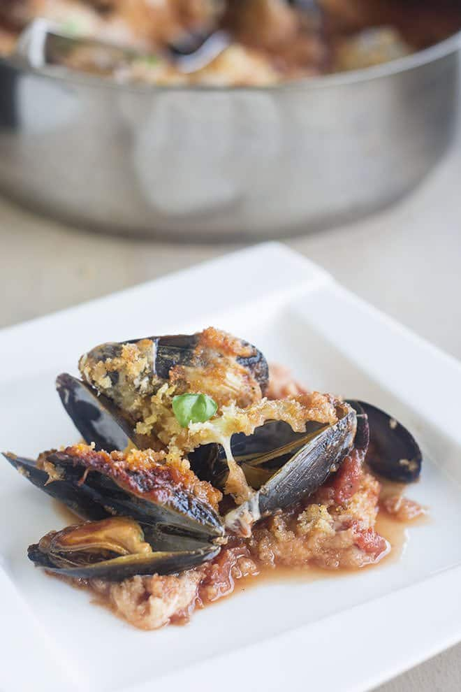 You've gotta try this new riff on Chicken Parmesan. It's Mussels Parmesan. It's made by steaming mussels in a delicious tomato sauce and then topping them with lots of mozzarella and crunchy breadcrumbs.