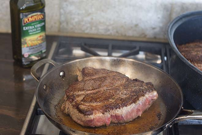 Beef chuck roast being seared in a skillet on the stove.