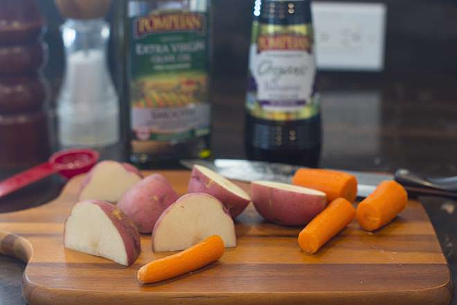 Red potatoes and carrots being cut on wooden cutting board.