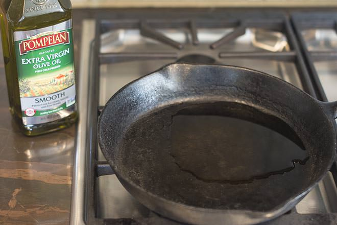 Olive oil in cast iron skillet heating on stove.
