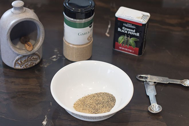 Salt, garlic powder, black pepper in background. White bowl with seasonings in it. Teaspoons to right.