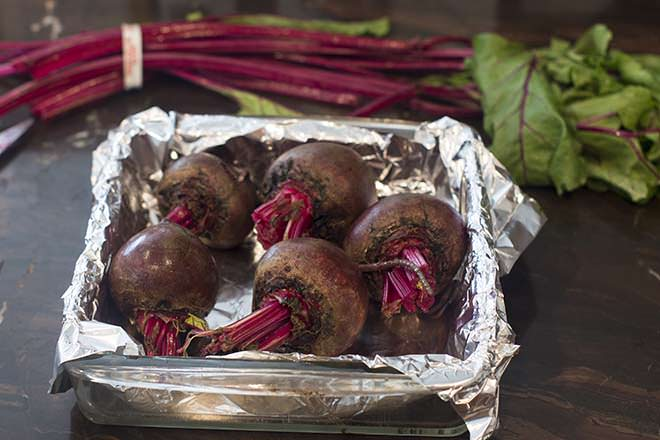 Five beets in a dish lined with foil.