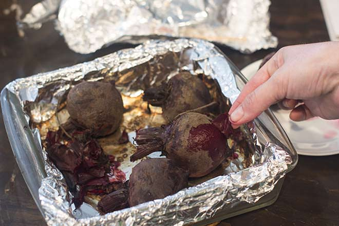 Peel skins off cooked beets.