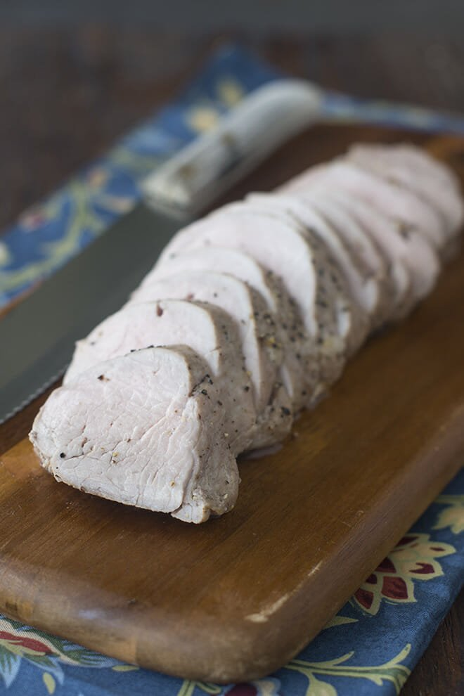 Sliced pork tenderloin on a wooden cutting board.