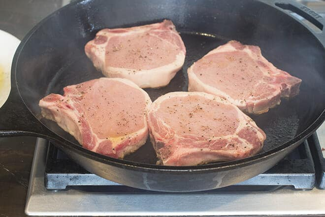 Four pork chops in a cast iron skillet on the stove.