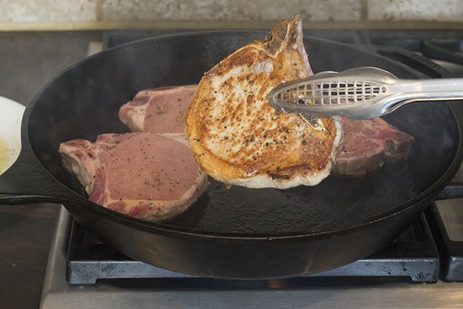 Tongs flipping over a pork chop, three additional pork chops in the cast iron skillet.