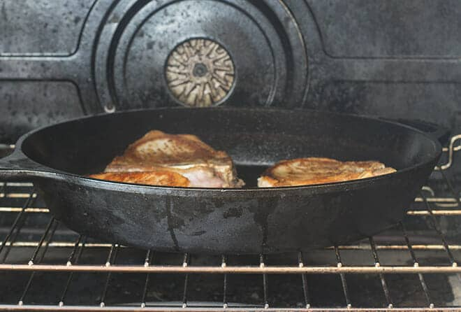 Uncovered cast iron skillet with pork chops in the oven.
