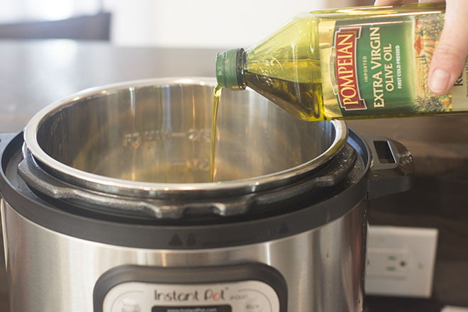 Olive oil being drizzled into an instant pot.