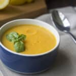 Learn how to make a creamy and delicious vegan butternut squash soup that has a few surprising but harmonious flavors in it, including coconut milk and basil.