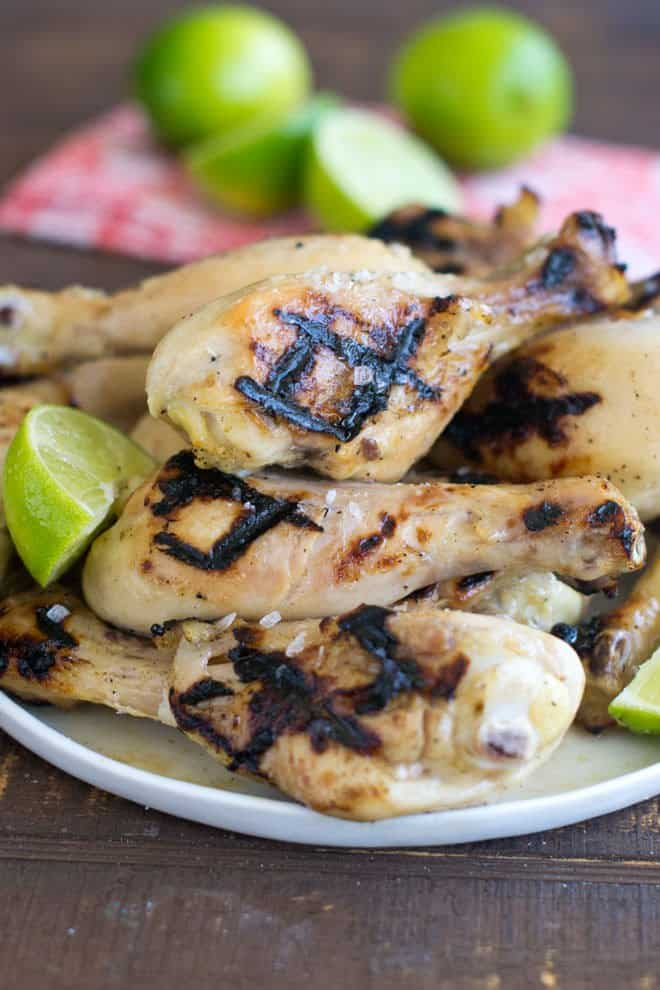Grilled Chicken Legs with lime wedges piled on a plate.