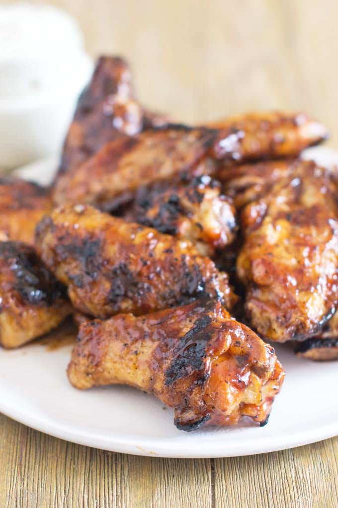 Grilled wings with bbq sauce piled on a plate.