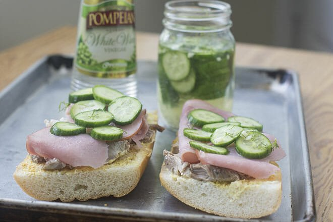 Open face Cuban Sandwiches on a baking sheet topped with quick pickles.