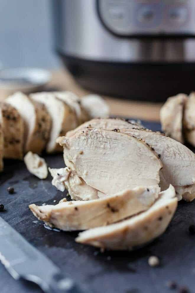 Sliced chicken breasts in front of an Instant Pot.