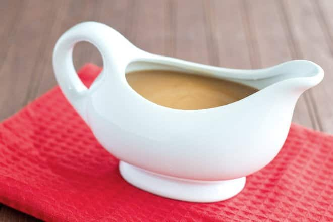 Gravy in a white gravy boat on a red kitchen towel.