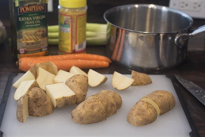 Potatoes cut in quarters on a cutting board.