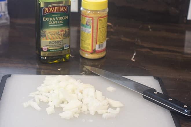 Chopped onion on cutting board.