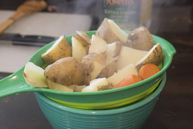 Potatoes and veggies being drained with colander and bowl.