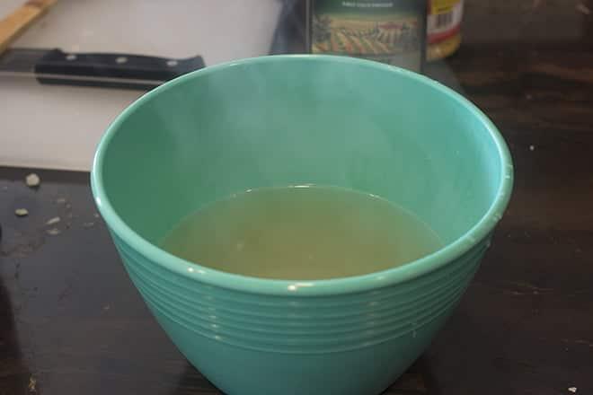 Homemade veggie broth in blue bowl.