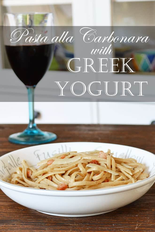 """A pasta dish full of flat linguine noodles and pieces of Canadian bacon in sauce. There's a glass of red wine behind it. The words """"Pasta alla Carbonara with Greek Yogurt"""" appear on the image."""