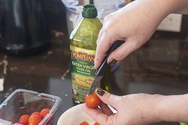 Next, use a paring knife to cut around the top of a cherry tomato.