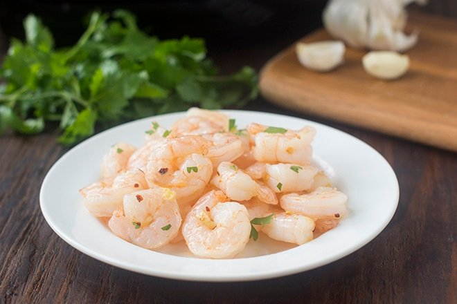 Pile of cooked shrimp in shallow white bowl.